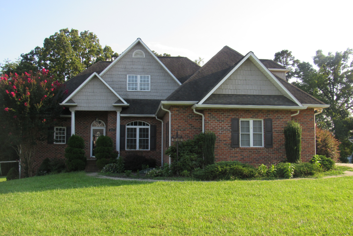 Exterior of brick 1.5 story house with yard