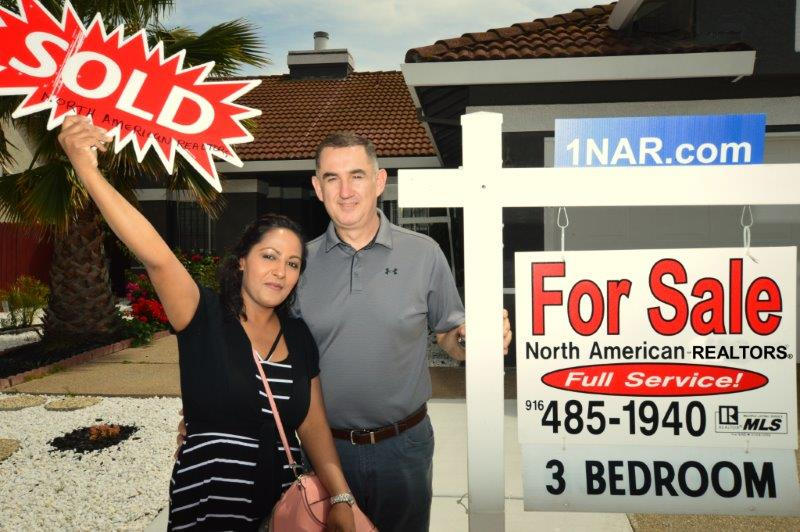 Sellers standing outside their home next to our real estate for sale sign holding a SOLD sign happy because the home is SOLD